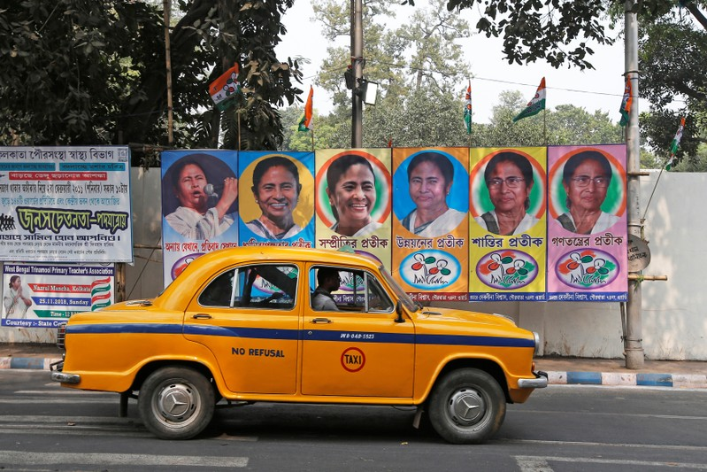 A taxi drives past a poster of Mamata Banerjee, Chief Minister of West Bengal state, in Kolkata