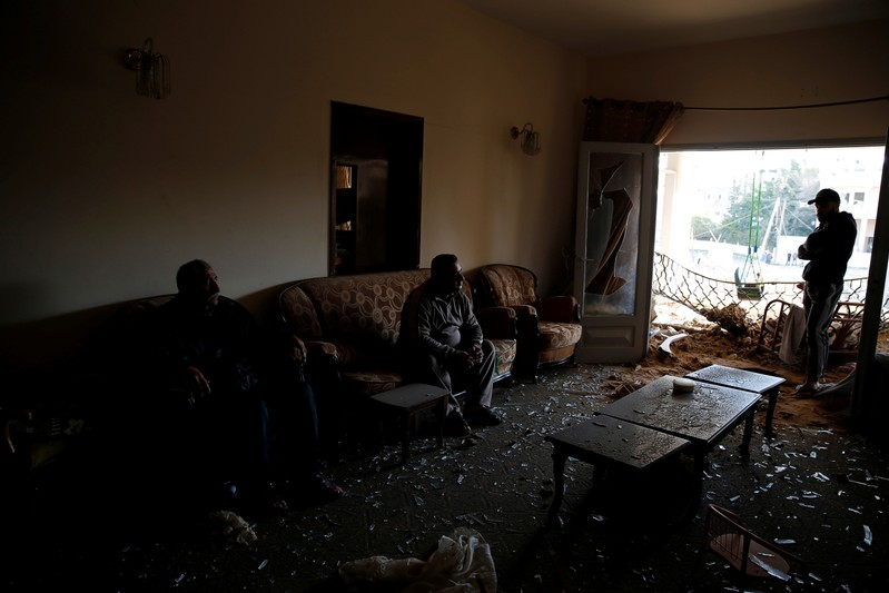 Palestinians sit inside their house that was damaged in a nearby Israeli air strike in Gaza City