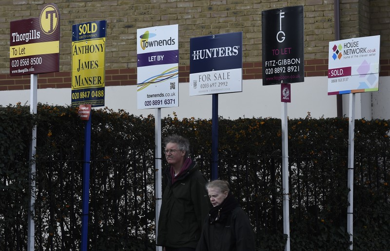 A couple walk past property estate agent sales and letting signs in London, Britain