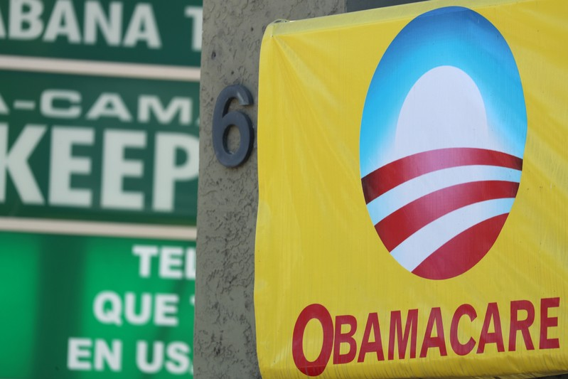 FILE PHOTO - A sign on an insurance store advertises Obamacare in San Ysidro
