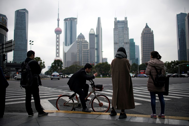 FILE PHOTO: People stand on the sidewalk at Lujiazui financial district in Pudong, Shanghai