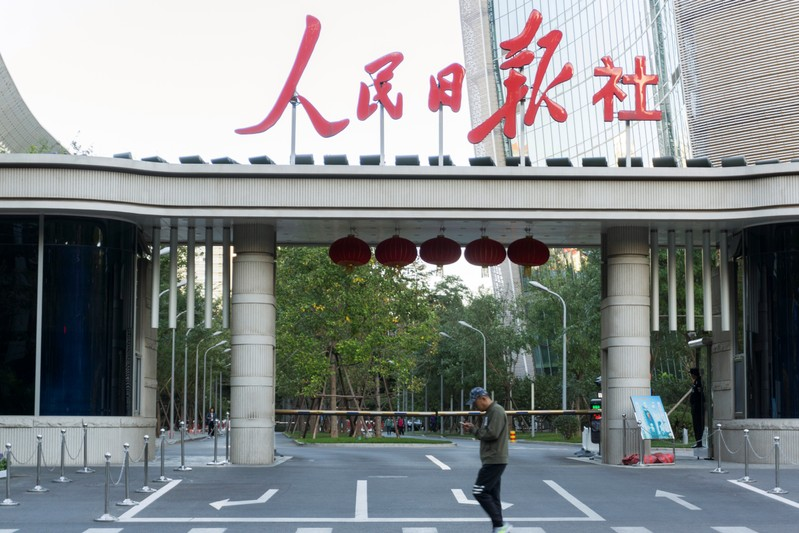 Man holding a smartphone walks past the headquarters of Chinese state newspaper People's Daily in Beijing