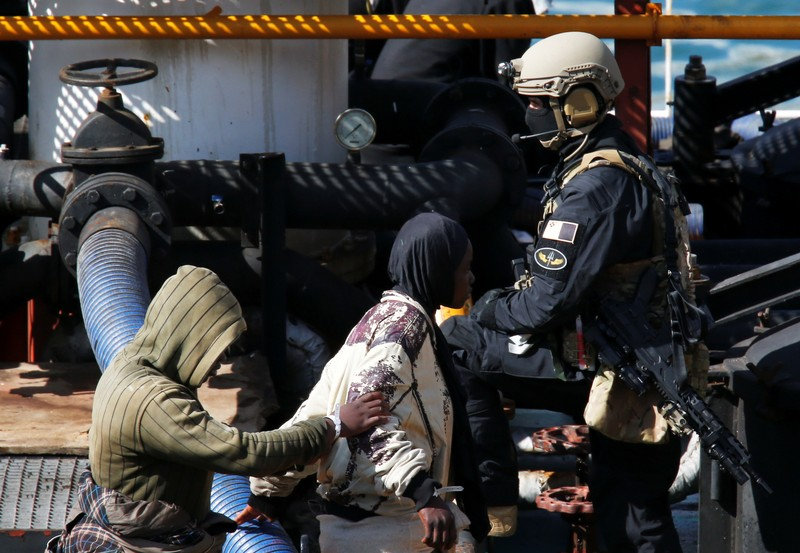 A Maltese special forces soldier guards a group of migrants on the merchant ship Elhiblu 1 after it arrived in Senglea
