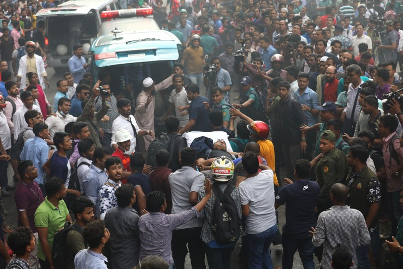 A rescued person is taken to the ambulance as fire broke out at a multi-storey commercial building in Dhaka