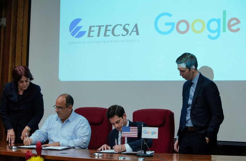 Google's Head of Strategy and Operations in Cuba, Brett Perlmutter, and Vice President of Investment of Etecsa, Luis Adolfo Reyes, sign documents in Havana