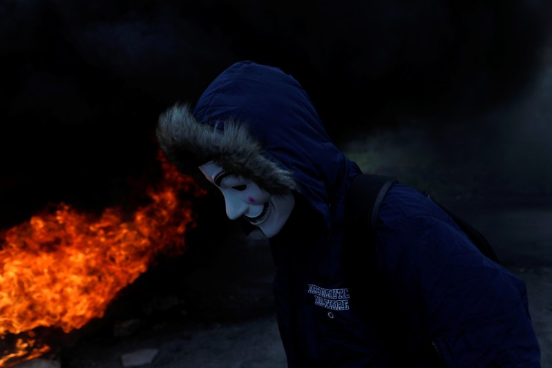 Palestinian demonstrator wearing a mask stands next to a burning tire during clashes with Israeli forces at a protest marking Land Day, near the Jewish settlement of Beit El, in the Israeli-occupied West Bank