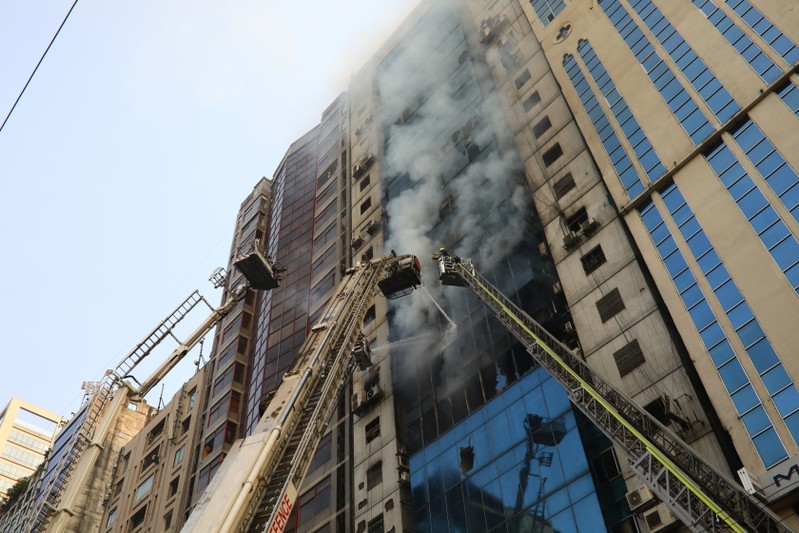 Firefighters attempt to extinguish a fire at a multi-storey commercial building in Dhaka