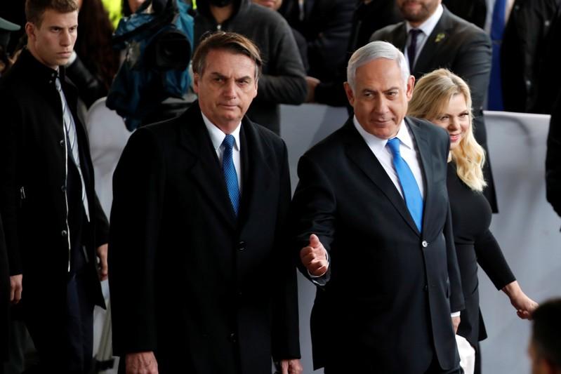 Israeli Prime Minister Benjamin Netanyahu gestures as he stands next to Brazilian President Jair Bolsonaro during a welcoming ceremony upon his arrival in Israel, at Ben Gurion International airport in Lod, near Tel Aviv, Israel