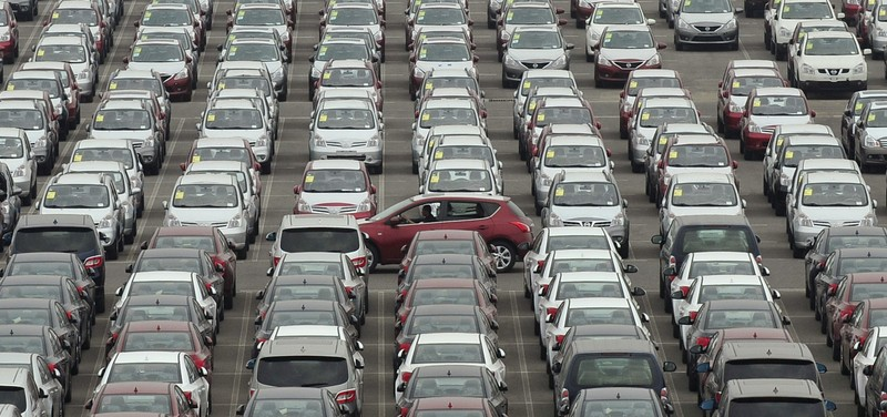 FILE PHOTO: Man drives red car past parking lot where large numbers of newly manufactured cars are parked at Dayaowan port of Dalian