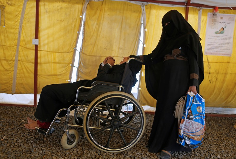 Woman sits in a wheelchair as she waits for medical care at a cholera treatment center in Sanaa