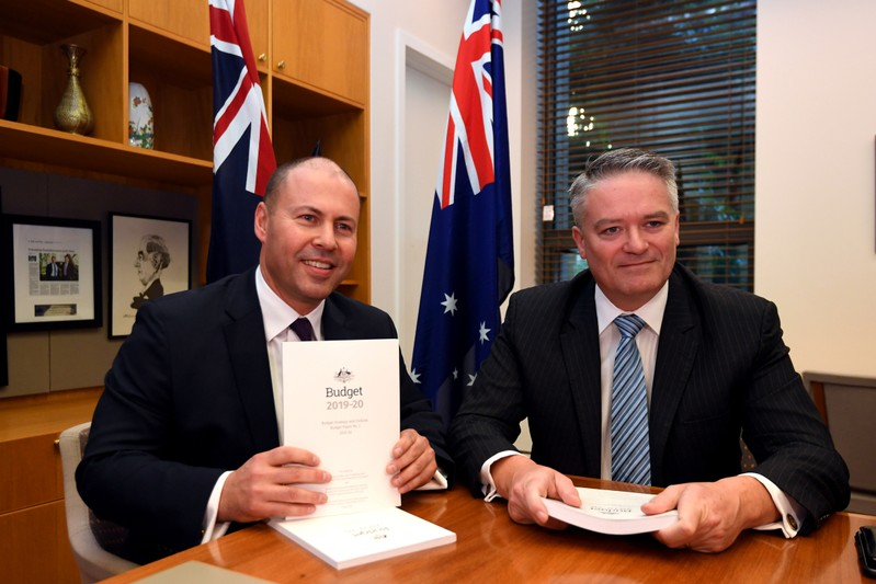 Treasurer Josh Frydenberg poses for a photograph with Minister for Finance Mathias Cormann with the 2019 Budget papers ahead of Budget 2019 at Parliament House in Canberra