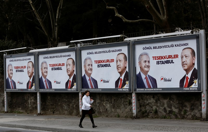 A woman walks past by AK Party billboards with pictures of Turkish President Tayyip Erdogan and mayoral candidate Binali Yildirim in Istanbul