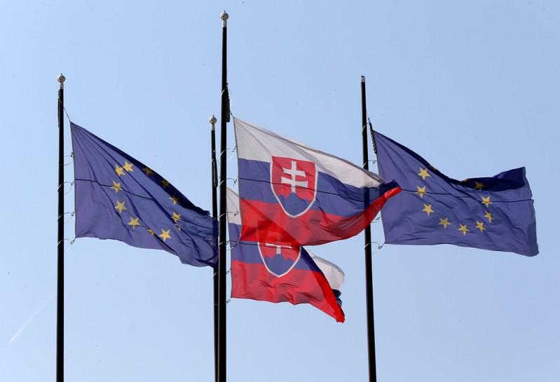 FILE PHOTO: European Union and Slovakian flags are seen outside the Bratislava Castle (Hrad) ahead of an upcoming European Union summit in Bratislava