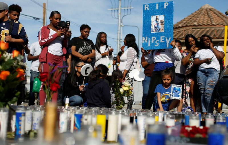 People gather around a makeshift memorial for Grammy-nominated rapper Nipsey Hussle who was shot and killed outside his clothing store in Los Angeles