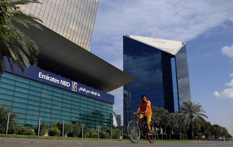 A man rides a bicycle past Emirates NBD head office in Dubai