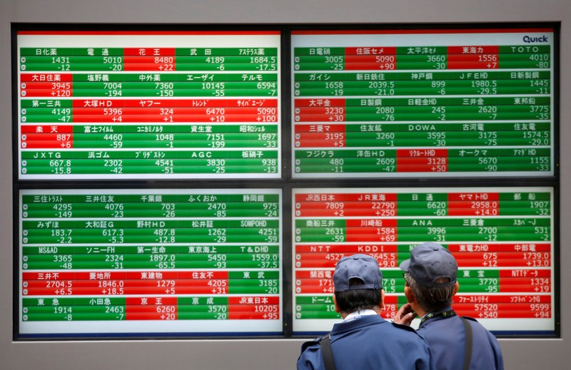 FILE PHOTO: Men look at stock quotation boards outside a brokerage in Tokyo