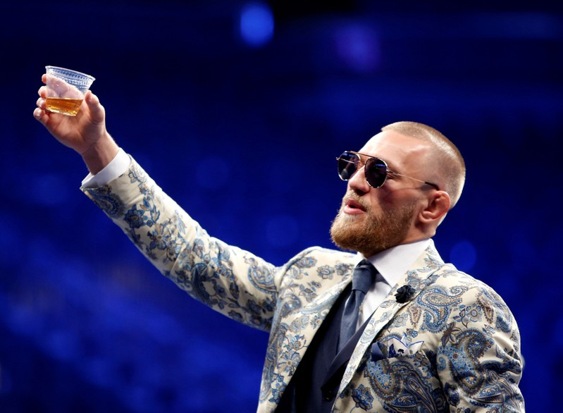 FILE PHOTO: UFC lightweight champion Conor McGregor of Ireland raises a cup of Irish whiskey during post-fight news conference at T-Mobile Arena in Las Vegas