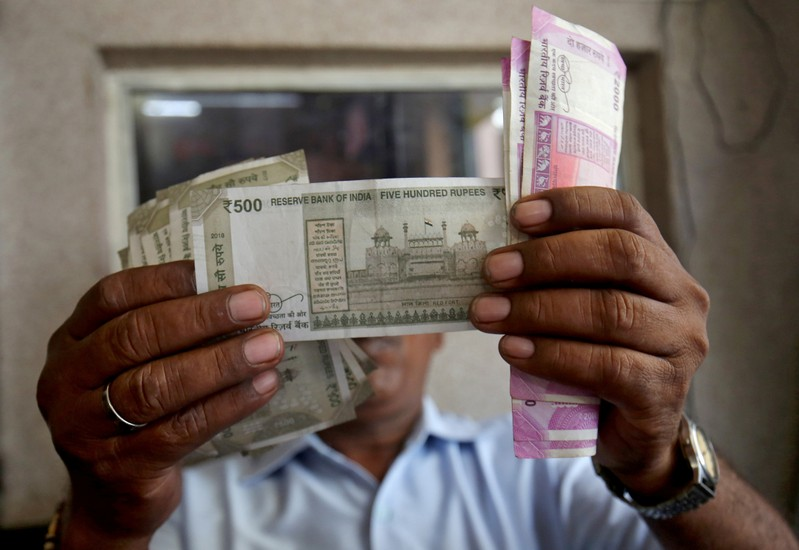 A cashier checks Indian rupee notes inside a room at a fuel station in Ahmedabad