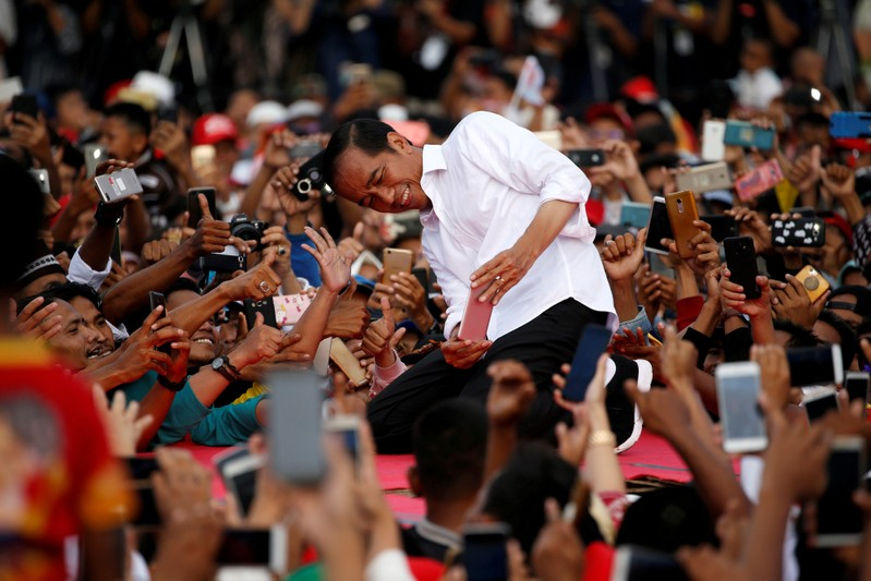 FILE PHOTO: Indonesia's presidential candidate for the upcoming general election Joko Widodo takes pictures with his supporters during his first campaign rally at a stadium in Serang
