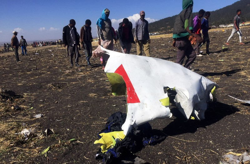FILE PHOTO: People walk past a part of the wreckage at the scene of the Ethiopian Airlines Flight ET 302 plane crash, near the town of Bishoftu, southeast of Addis Ababa