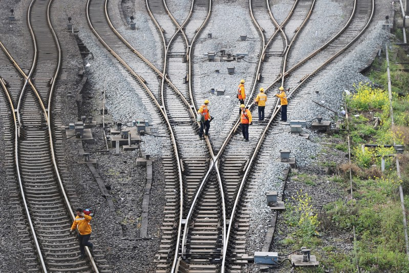 FILE PHOTO: Workers inspect railway tracks, which serve as a part of the Belt and Road freight rail route linking Chongqing to Duisburg, at the Dazhou railway station