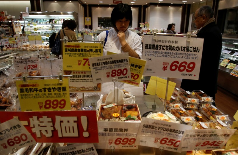 FILE PHOTO: Shopper looks at food at a supermarket in Tokyo
