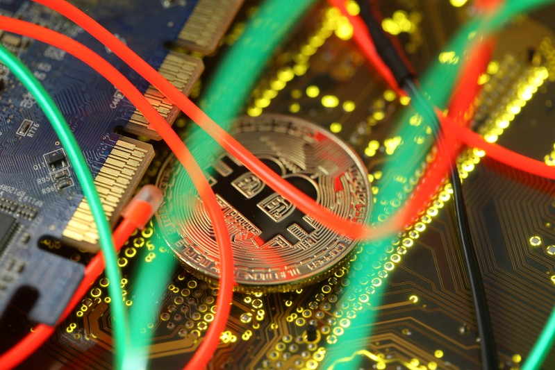 FILE PHOTO: Representation of the Bitcoin virtual currency standing on a PC motherboard