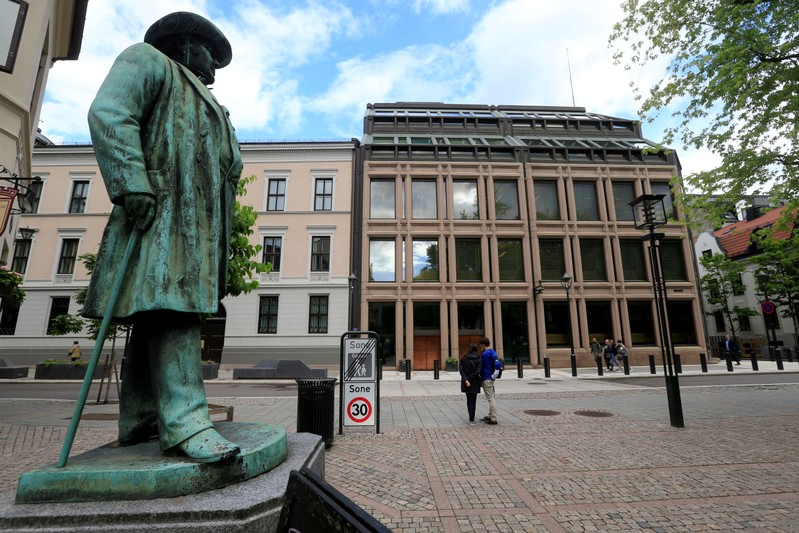 FILE PHOTO: People go about their day near Norway's central bank building in Oslo