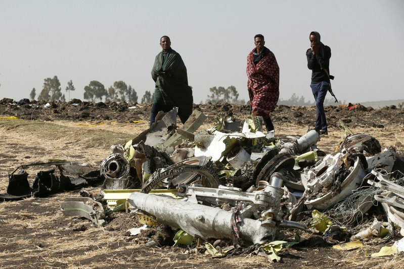 FILE PHOTO: Ethiopian police officers walk past the debris of the Ethiopian Airlines Flight ET 302 plane crash, near the town of Bishoftu, near Addis Ababa