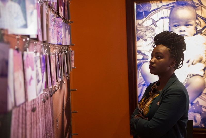 Aline Uwase, a Rwandan genocide survivor looks at the pictures of victims donated by survivors inside at the Genocide Memorial in Gisozi within Kigali