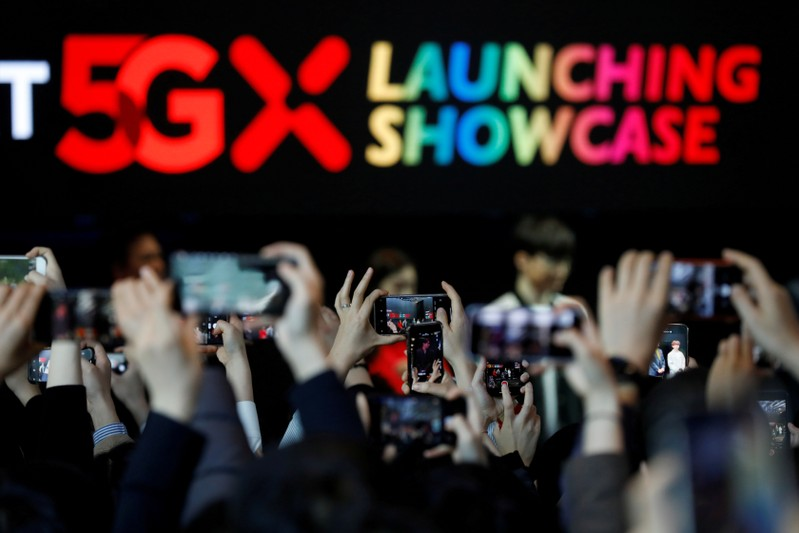 FILE PHOTO: People take photographs during a launching ceremony for SK Telecom's 5G service, in Seoul