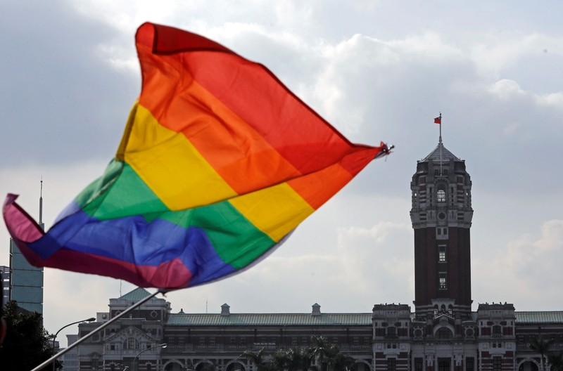 FILE PHOTO: A participant waves a rainbow flag in front of President's office building during LGBT pride parade in Taipei