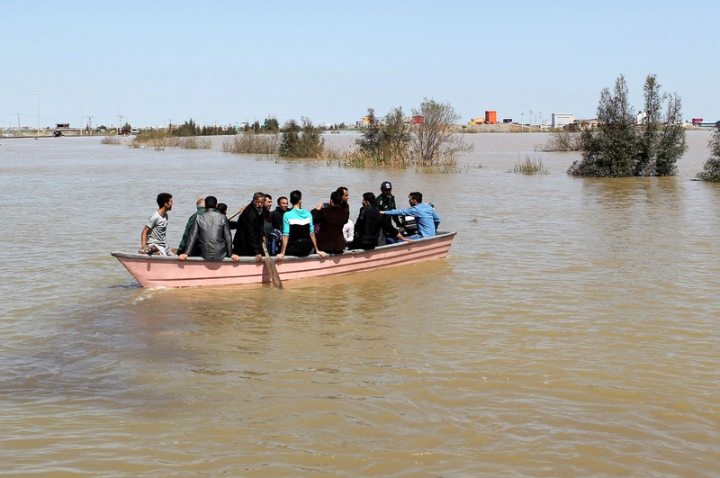 FILE PHOTO: People are seen on a boat after a flooding in Golestan province