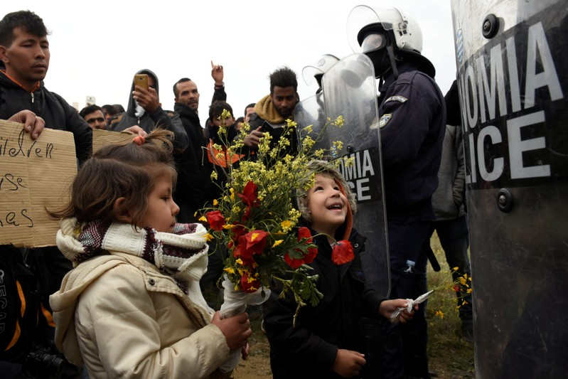 Migrant children hold flowers as they stand in front of riot police officers next to a camp in the town of Diavata in northern Greece