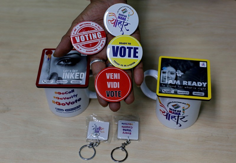 An election official displays badges, key chains and mugs to be distributed among the people to encourage them to cast their vote, in Kolkata