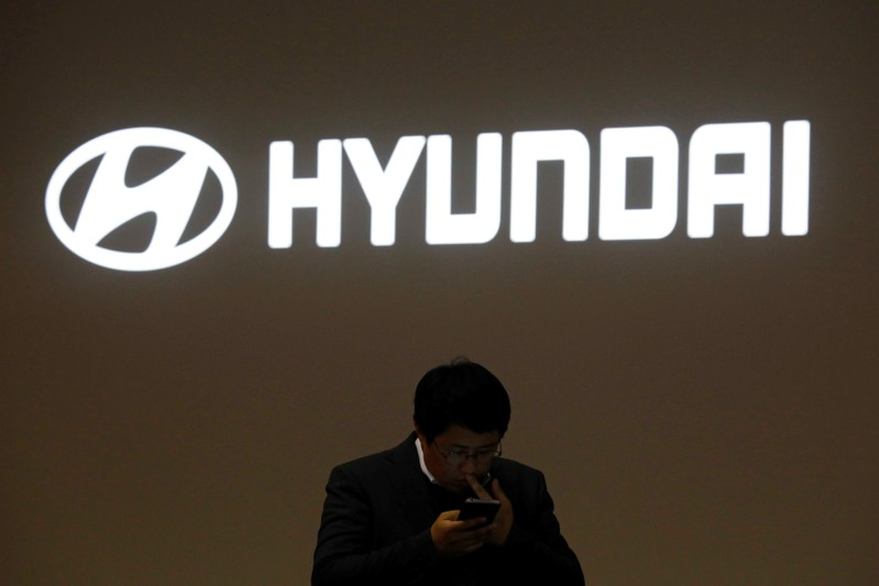 A man walks past the logo of Hyundai Motor during the 2019 Seoul Motor Show in Goyang