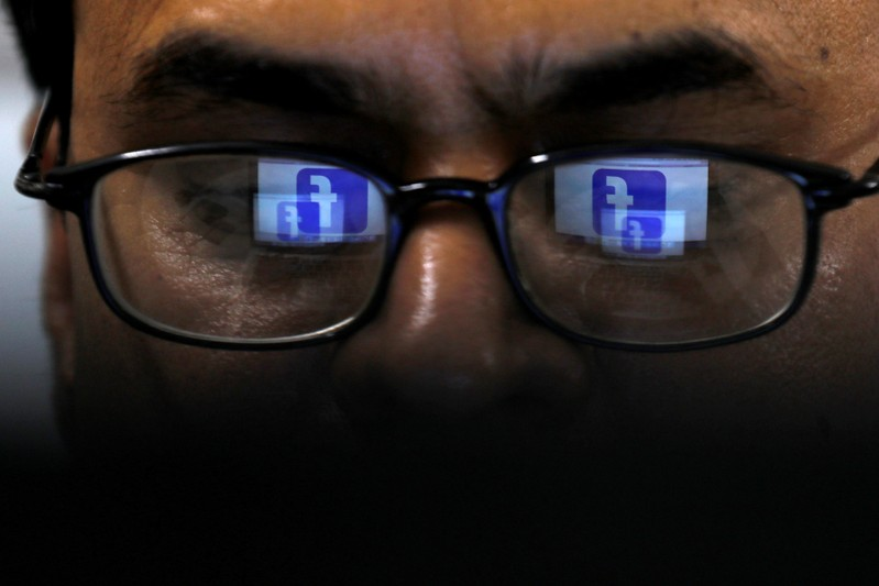 FILE PHOTO: Facebook logo is reflected in glasses in this picture illustration