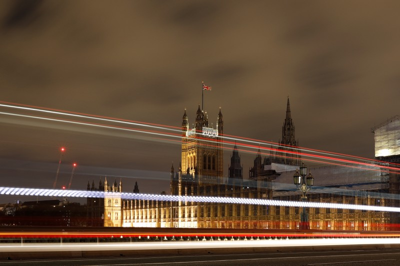 Cars drive over Westminster Bridge as the Houses of Parliament is seen in the background, in Westminster, central London