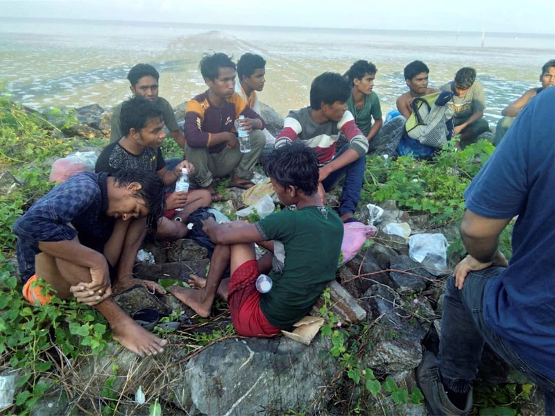 Dozens of people, believed to be Rohingya Muslims from Myanmar who were dropped off from a boat are pictured on a beach near Sungai Belati, Perlis, Malaysia