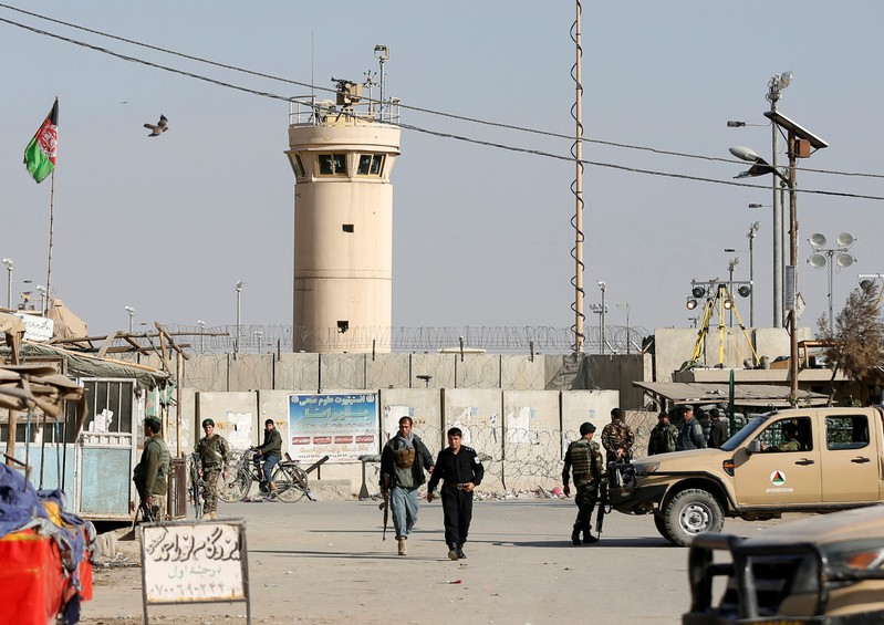 Afghan National Army (ANA) soldiers and police keep watch outside the Bagram Airfield entrance gate, after an explosion at the NATO air base, north of Kabul
