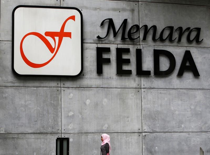 FILE PHOTO:  A woman walks past a logo of Felda in Kuala Lumpur