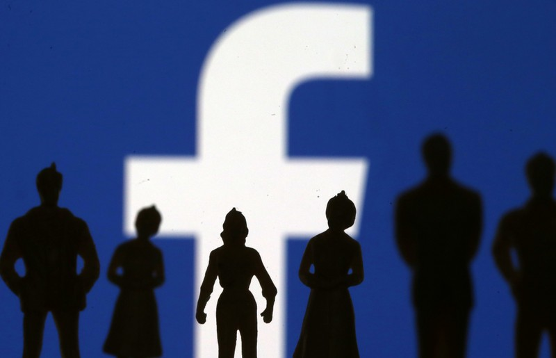 FILE PHOTO - Small toy figures are seen in front of Facebook logo in this illustration picture