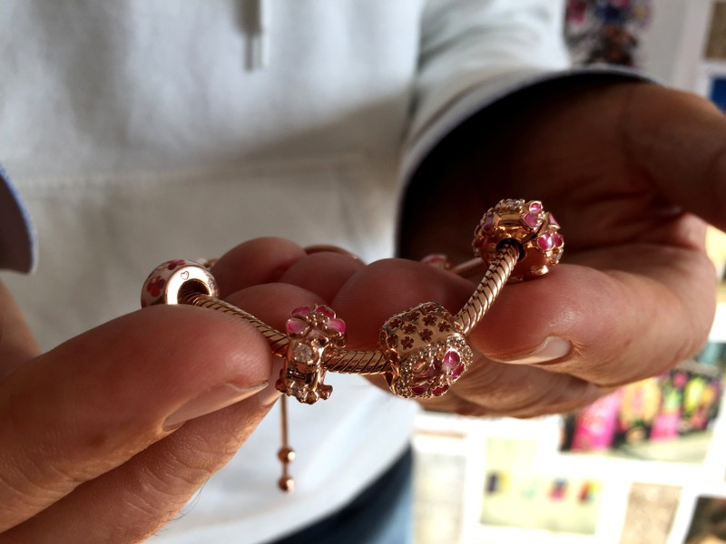 A Pandora employee shows a piece from the new jewelry collection Peach Blossom in the company's headquarters in Copenhagen