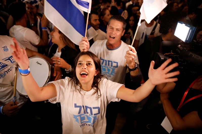 Supporters of Benny Gantz's Blue and White party react to exit polls in Israel's parliamentary election at the party headquarters in Tel Aviv, Israel