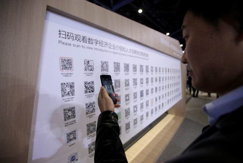 A man uses mobile phone to scan the QR codes for job-seeking information during an internet expo at the fifth WIC in Wuzhen