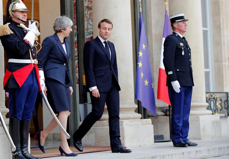 French President Emmanuel Macron and British Prime Minister Theresa May leave after a meeting to discuss Brexit, at the Elysee Palace in Paris