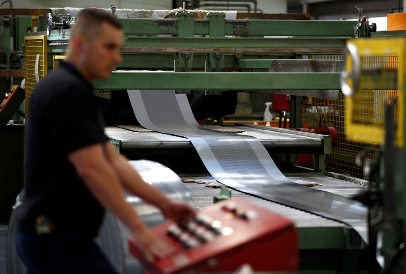 A worker at perforating company Bion uses a machine at the factory in Reading