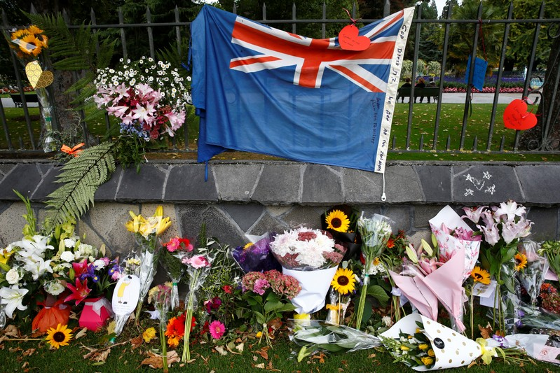 Flowers and a New Zealand national flag are seen at a memorial as tributes to victims of the mosque attacks near Linwood mosque in Christchurch