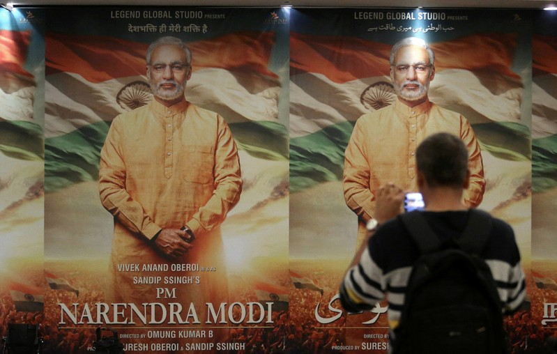 FILE PHOTO: A man uses his mobile phone to take photographs of a poster of the upcoming film