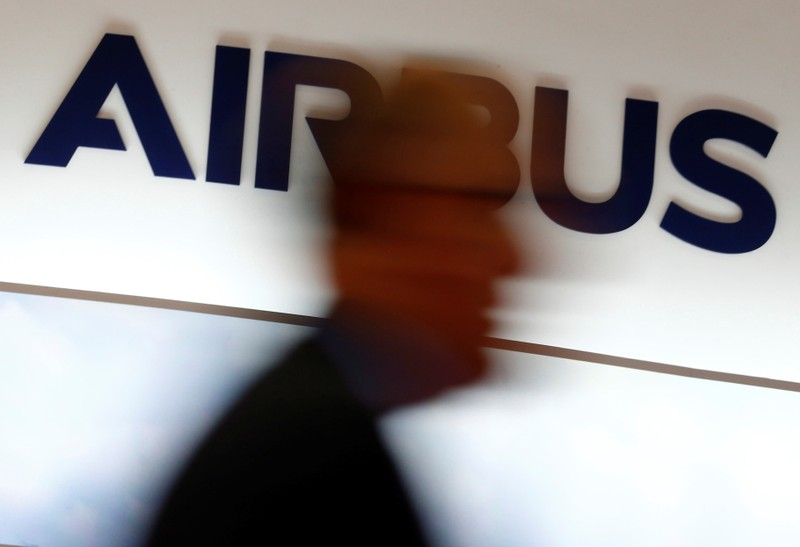 A man walks past an Airbus logo at the Langkawi International Maritime and Aerospace Exhibition in Langkawi